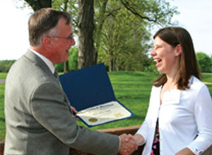 Dean Woolliscroft presents Lisa Whitehead (M.D. 2007) with a scholarship certificate at the Dean's Merit Scholar Reception last May.