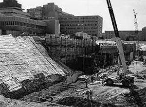 The University Hospital construction site in 1981, looking southwest, with C.S. Mott Children's Hospital and Old Main in the background