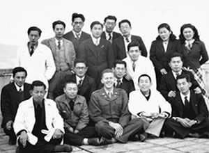 Anderson (front row, center) and members of his genetics staff on the roof of the Hiroshima Red Cross Hospital on January 10, 1949