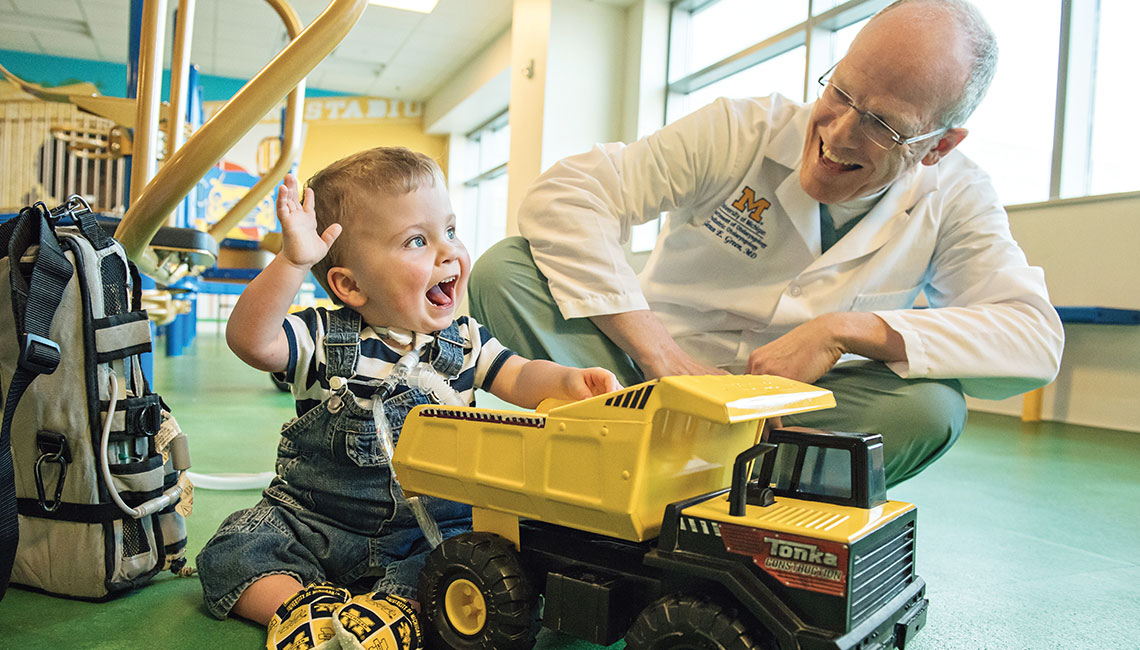 Levi Berens' joy lights up a playroom at Mott as he plays with Glenn Green, M.D., the surgeon who brought hope and health to the toddler.