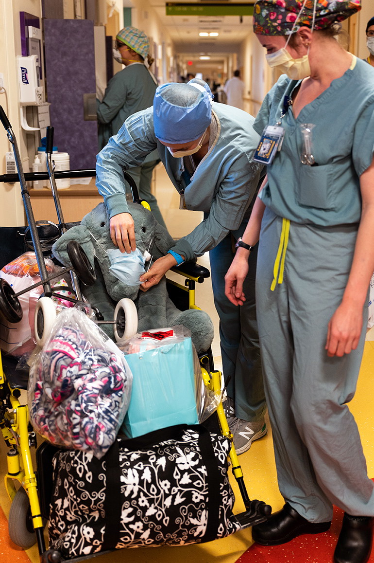 "Davis, RN, and her stuffed animal are discharged on April 25, two weeks after she was admitted to Michigan Medicine for COVID-19. The elephant was a gift from a fellow PICU nurse ""who felt I needed a cuddle buddy since I was in the hospital,"" Davis says of Schubert the elephant."