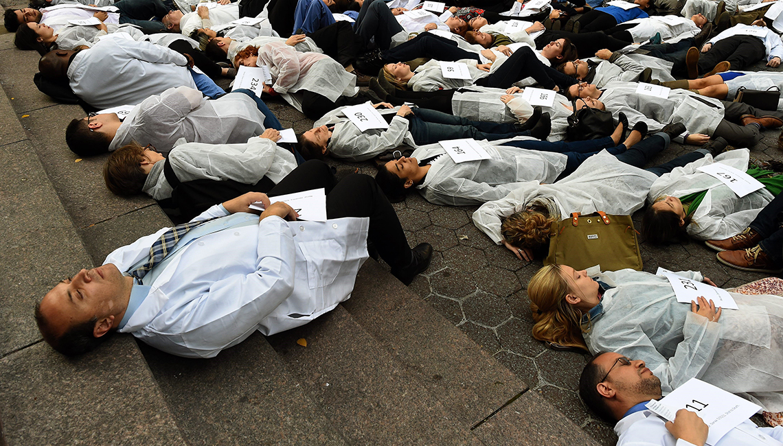 "Health workers participate in a ""die-in"" near the United Nations in New York City to draw attention to attacks on Syrian hospitals."