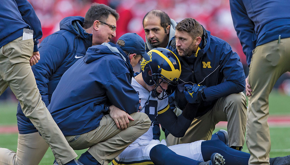 Asheesh Bedi and other members of the U-M Athletics medical team tend to injured quarterback Brandon Peters