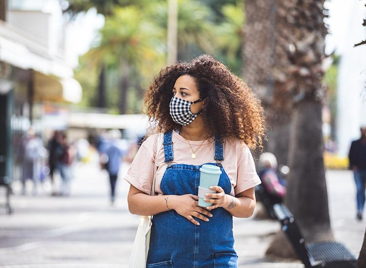Pregnant woman walking in the city in a sunny day protecting herself with a cloth face mask