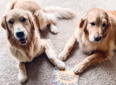 Fawn & Denver with a sign supporting the Frontline Super Heroes