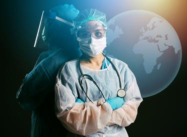 Medical professional wearing mask, safety glasses, gloves and face shield standing in front of the globe
